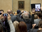 PARIS FRANCE - NOV 1ST 2013: Visitors at the Louvre Museum in Paris catch a glimpse of Leonardo Da Vinci's Mona Lisa on 1st November 2013.