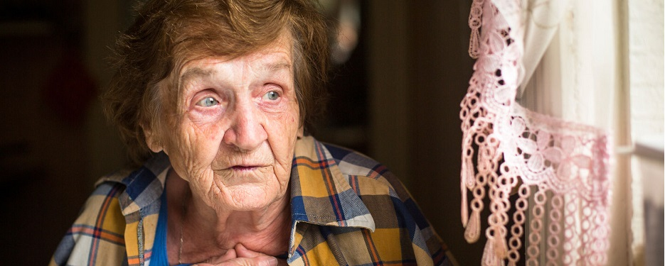 31323565 - old lonely woman sitting at a table near the window in his house. old age. loneliness.